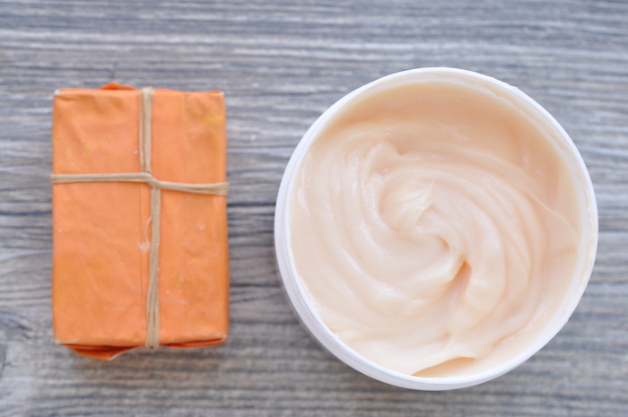 Large white can of body cream and handmade soap with orange packaging on a wooden surface